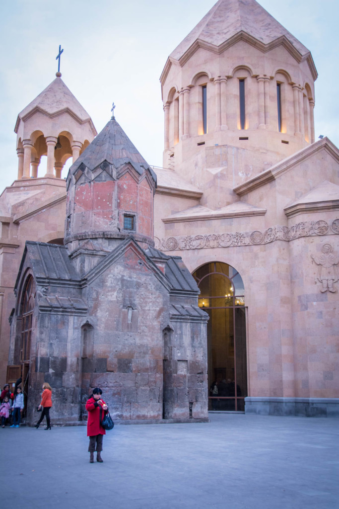 Easter in Armenia - A woman lighting a candle for Easter outside a church in the center of Yerevan, Armenia.