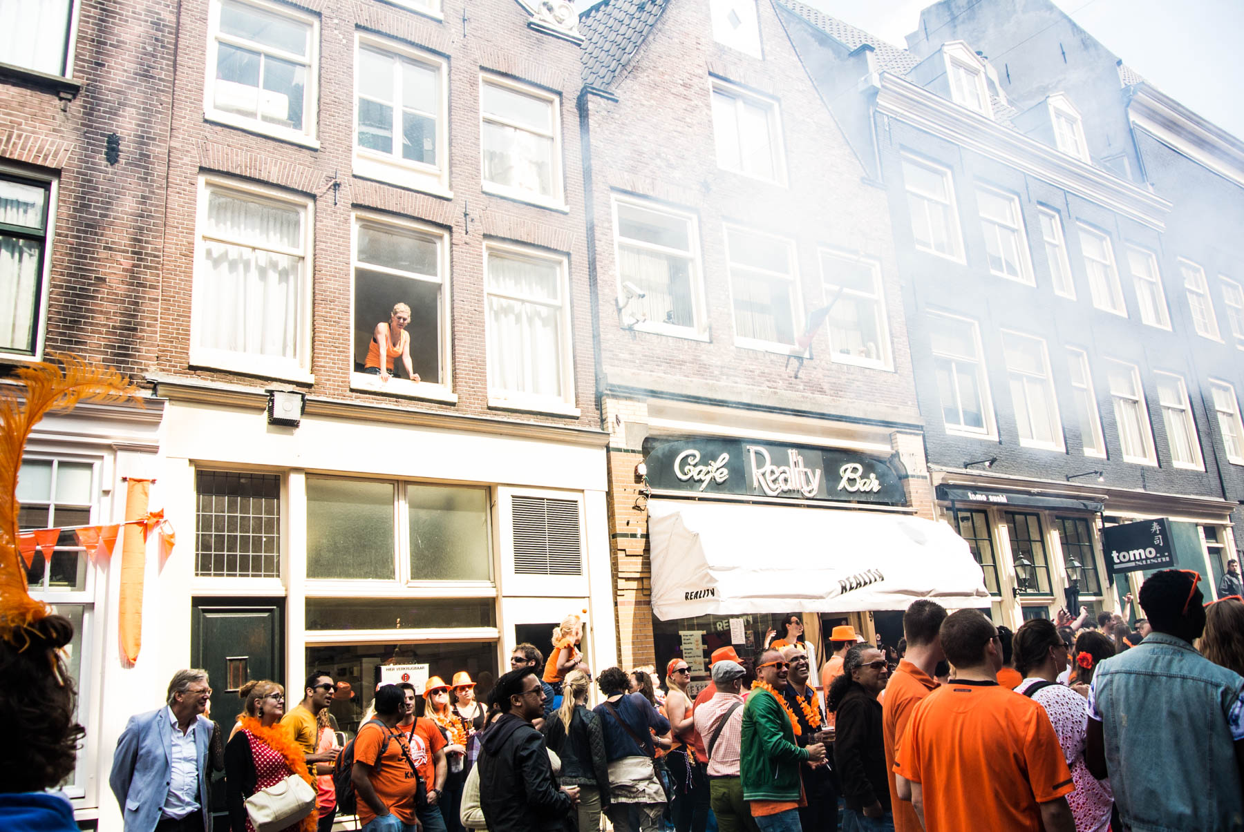 A woman watching over a party from a window during King's Day celebrations in Amsterdam.