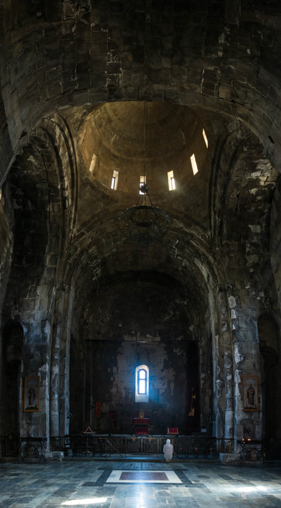 How to get to Tatev from Goris, Armenia - A woman praying in the dark and cool interior of Tatev monastery in Armenia.