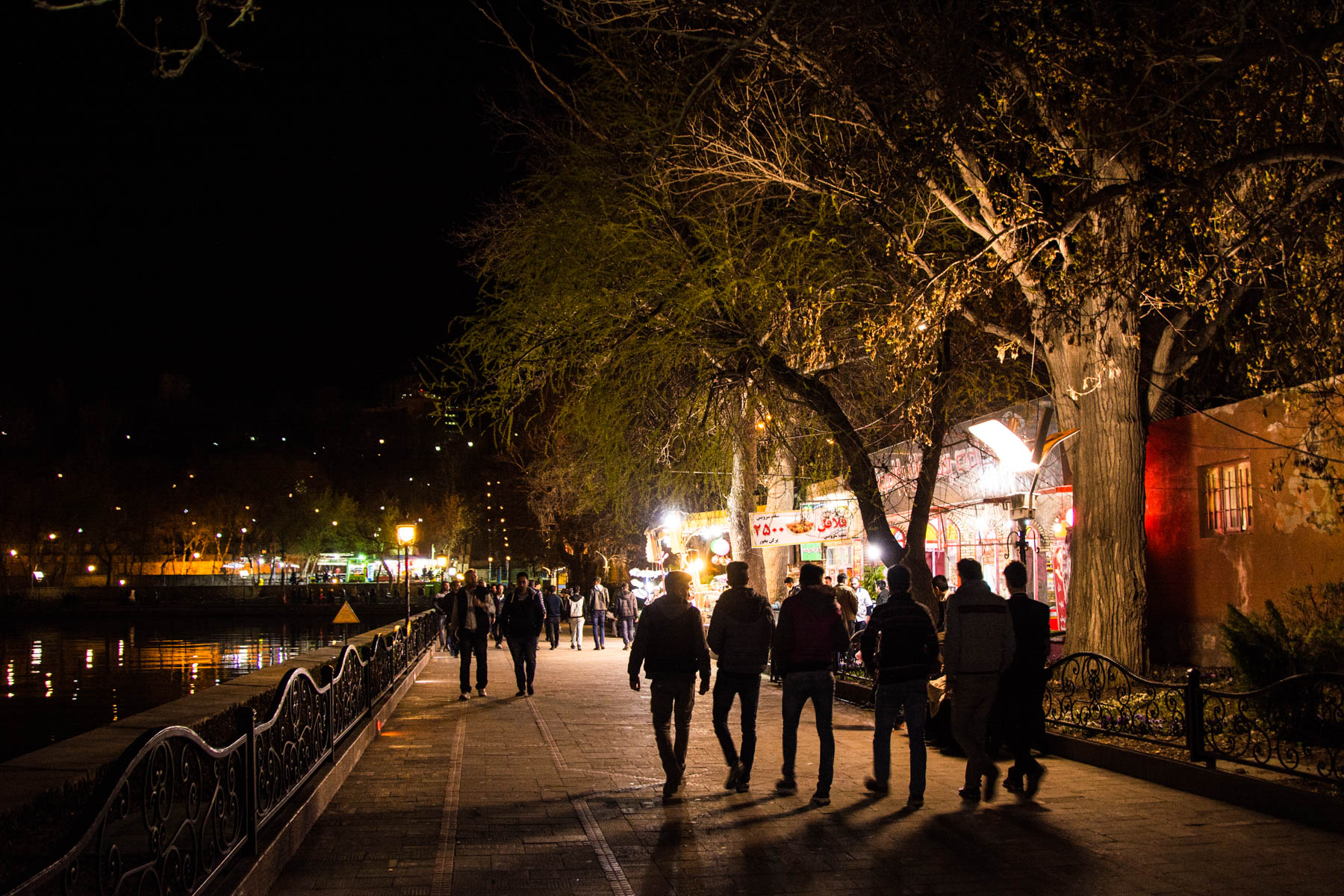 People walking around Shahgoli park in Tabriz, Iran at night.