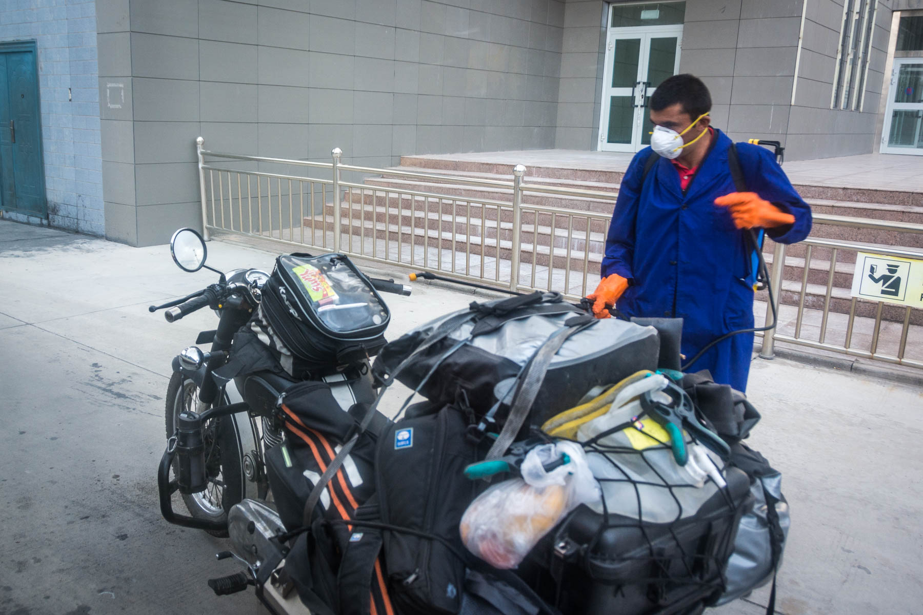Chinese man in Tashkargan disinfecting some motorbikes that have traveled through the Pakistan - China border crossing at the Khunjerab pass.
