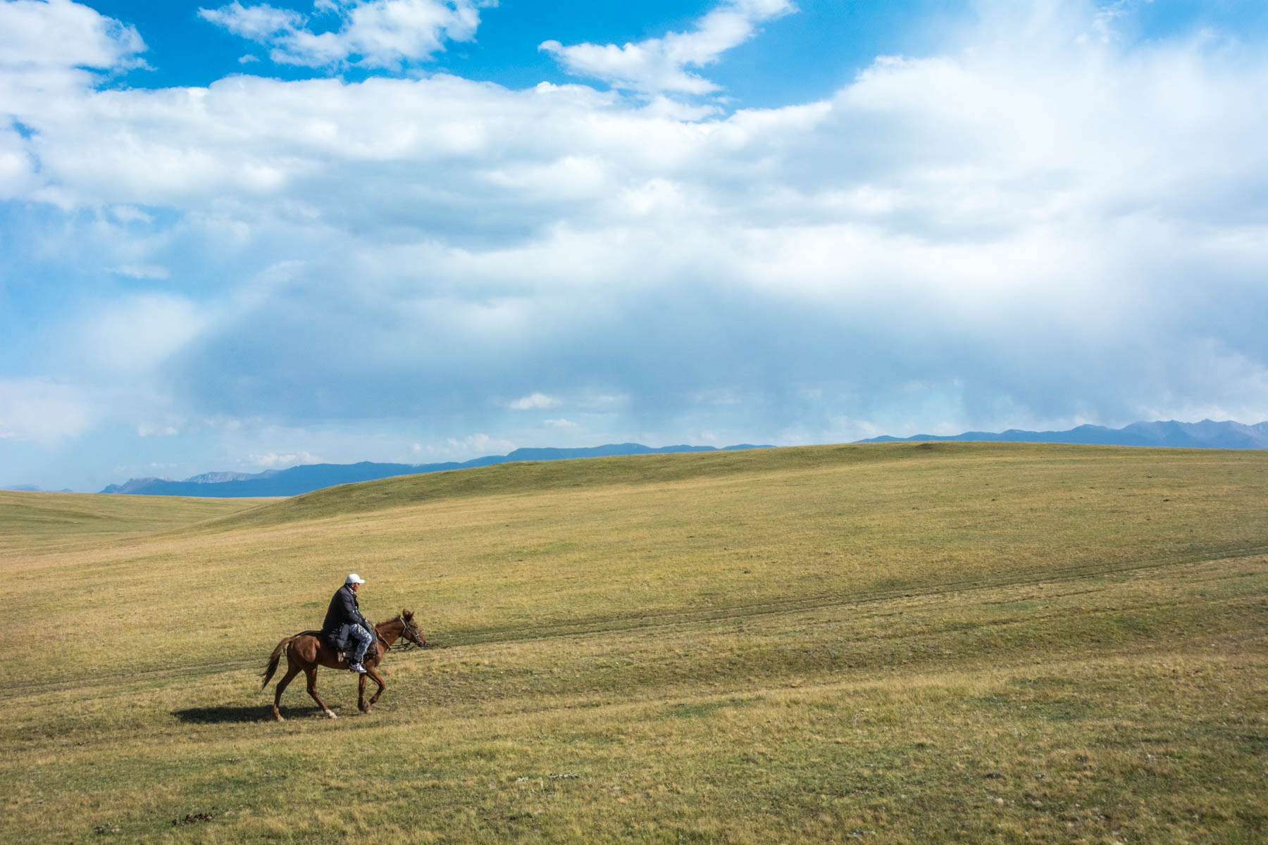 Horse guide riding through the steppe at Song Kul lake in Kyrgyzstan - Lost With Purpose