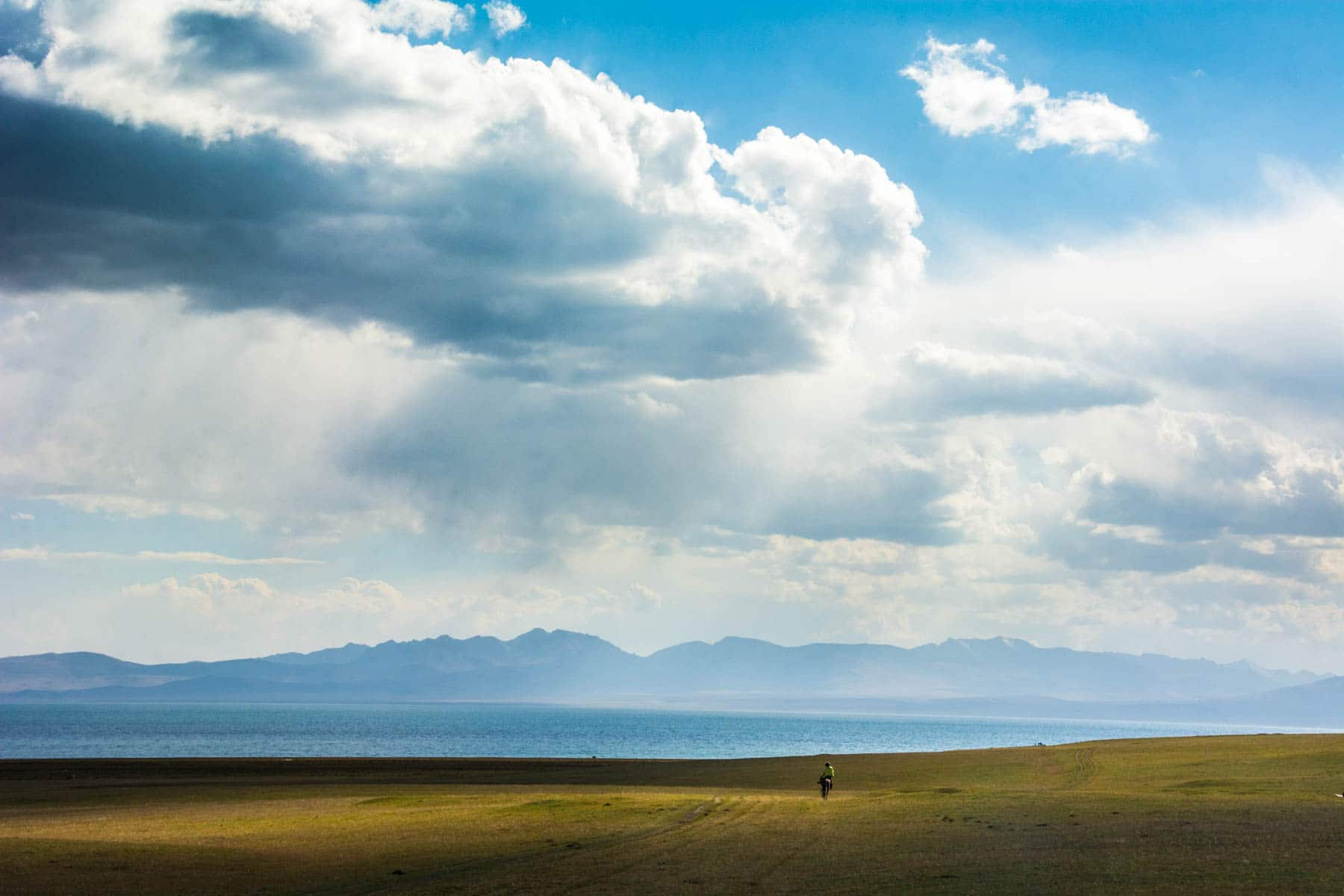 Riding through some golden sun rays at Song Kul lake in Kyrgyzstan - Lost With Purpose