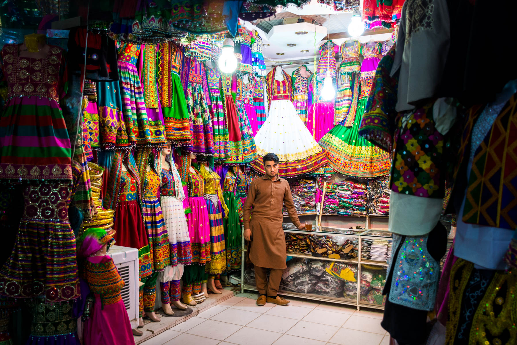 A boy standing in a colorful clothing bazaar in Mazar-i-Sharif, Afghanistan - Lost With Purpose