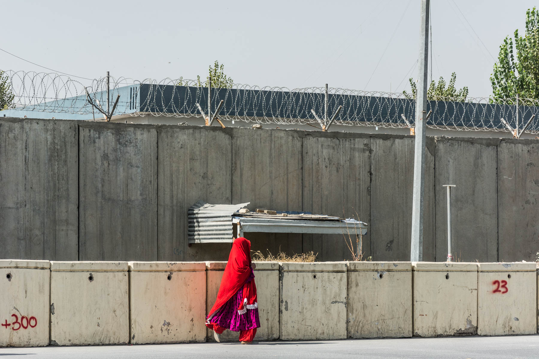 A girl walking in front of barbed wire and a concrete wall in Kabul, Afghanistan