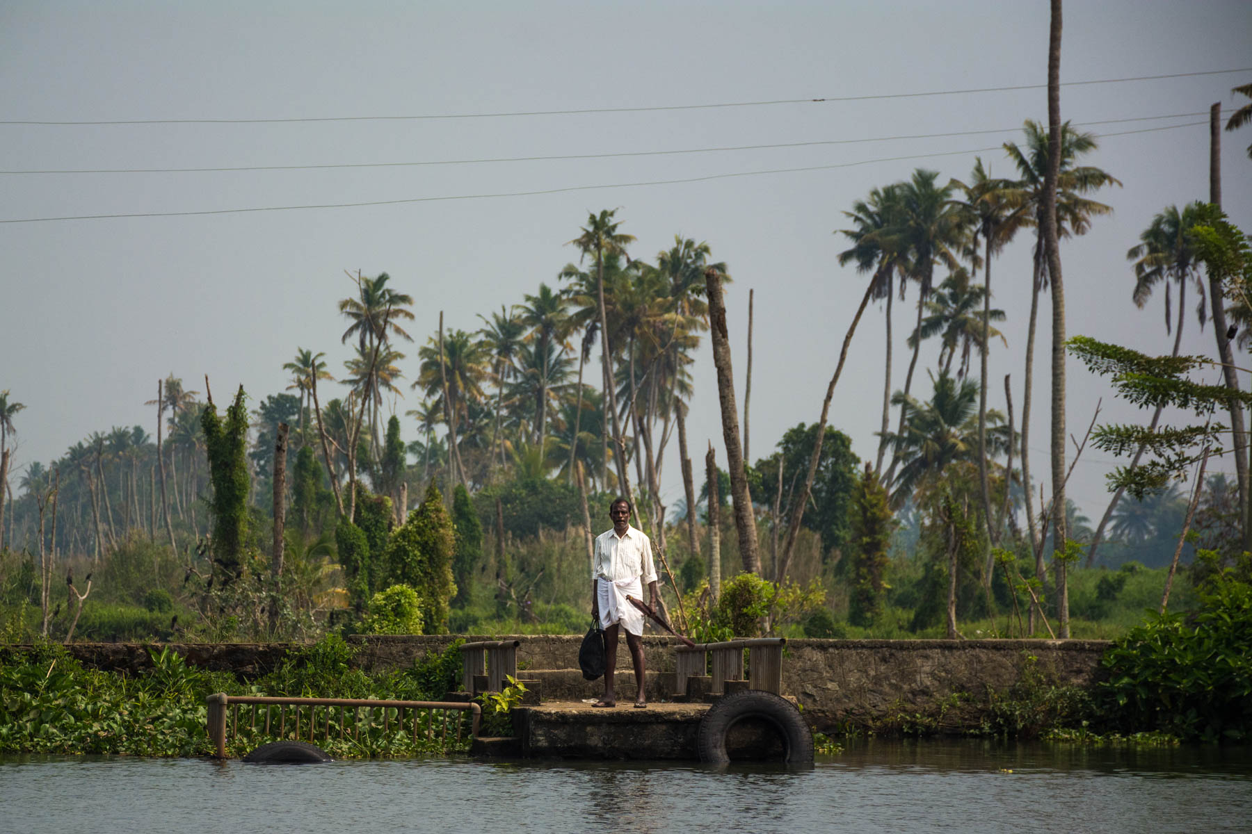 A man waiting for the budget ferry in Alleppey (Alappuzha), Kerala, India - Lost With Purpose