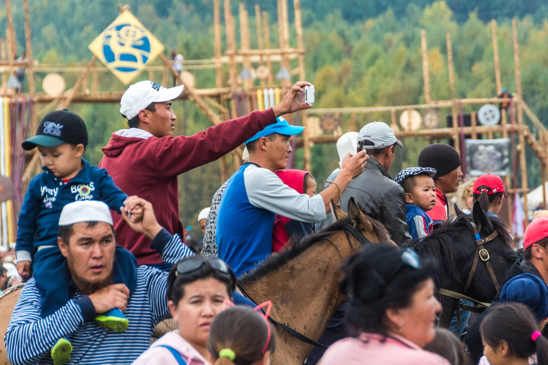 Men with phones on horseback at the World Nomad Games in Kyrgyzstan - Lost With Purpose
